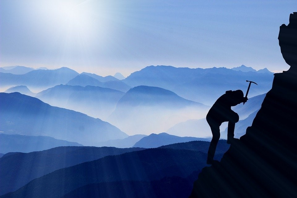alpiniste qui gravit une montagne dans la brume